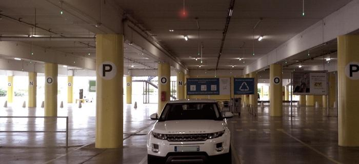 En röd lampa ovanför parkeringsplatsen indikerar att den är upptagen.